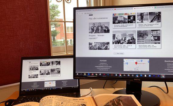 Två datorer med Arbetarrörelsens arkiv och biblioteks webbplats på skärmen. Fönster med röd gardin i bakgrunden.