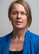 Forskaren Desirée Enlund i blå kavaj mot enfärgad grå bakgrund.