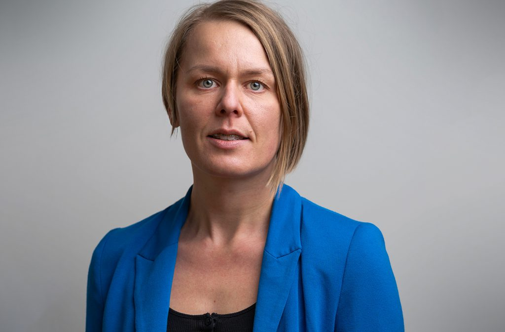 2020 års Rudolf Meidner-pristagare, Desirée Enlund,i blå kavaj mot grå bakgrund.