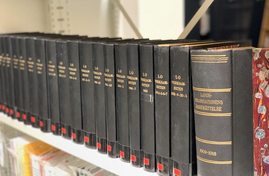 Lång rad med bokryggar i ARABs bibliotek. Böckerna är LO:s verksamhetsberättelser och de är svarta med guldtryck.