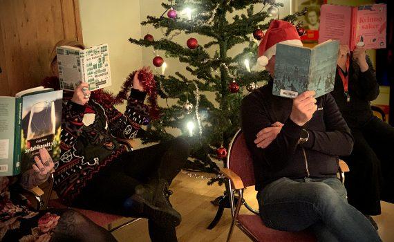 ARABs personal som läser varsin bok framför julgranen.