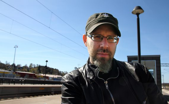 Professor Klas Rönnbäck på tågstation mot blå himmel.