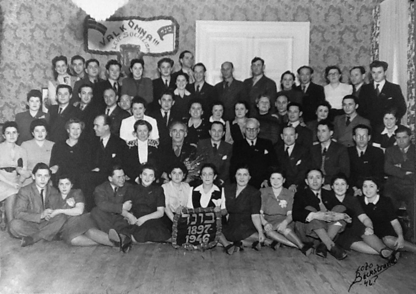 """Bundhemmet i Mälarbaden, Torshälla, i mars 1946. På väggen hänger en bild på Hjalmar Branting. På vepan står det """"Välkomna!!! Leve socialism"""". Foto: YIVO"""