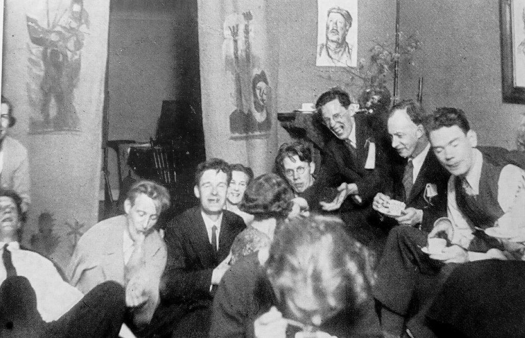 Svartvit bild som föreställer en uppsluppen fest hos arbetarförfattaren Rudolf Värnlund på 1930-talet. På bilden syns bland andra Josef Kjellgren (1:a från vänster), Rudolf Värnlund (2:a fr.v.), Gustav Sandgren (3:a från höger), Eyvind Johnson (2:a fr.h.) och Artur Lundkvist (1:a fr.h.).