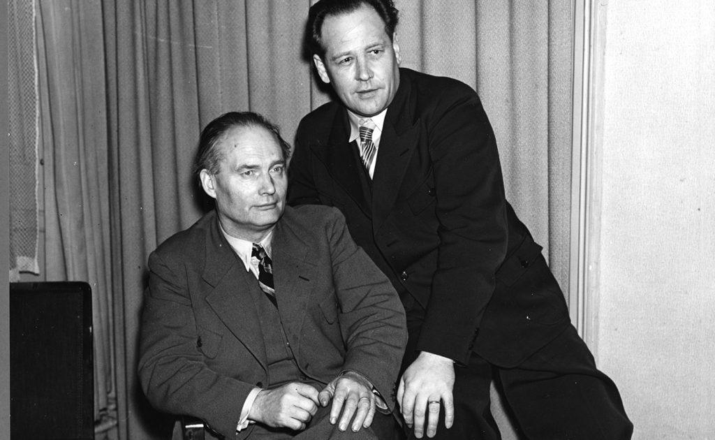 Albert Viksten (t v) iklädd en grå kostym, vis skjorta och slips på 1940-talet. Till höger syns en okänd man i mörk kostym som lutar sig mot Viksten.
