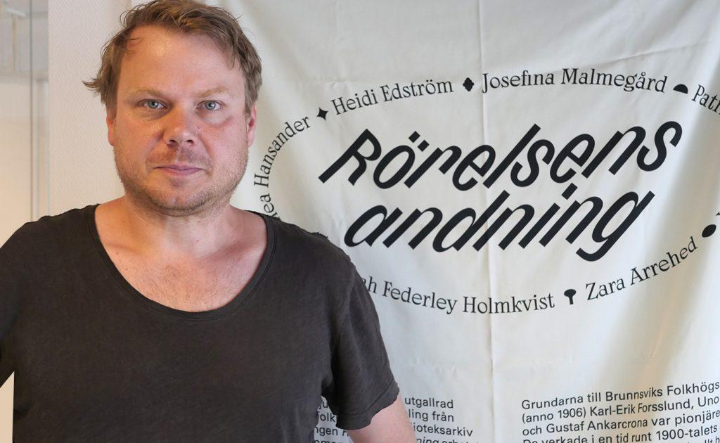 Konstnären Patrick Kretschek i svart t-shirt framför ett sidentyg där utställnningens namn, Rörelsens andning, är tryckt i svart.