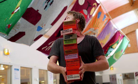 Konstnären Patrick Kretschek förbereder utställningen Rörelsens andning i ARABs bibliotek. Färgstarka ridåer hänger i taket.