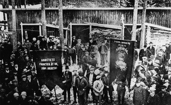 """Svartvit bild på fackföreningsmedlemmar 1917 vid Mariebergs sågverk i Ådalen, """"Arbetets frukter åt de, som arbeta!"""""""
